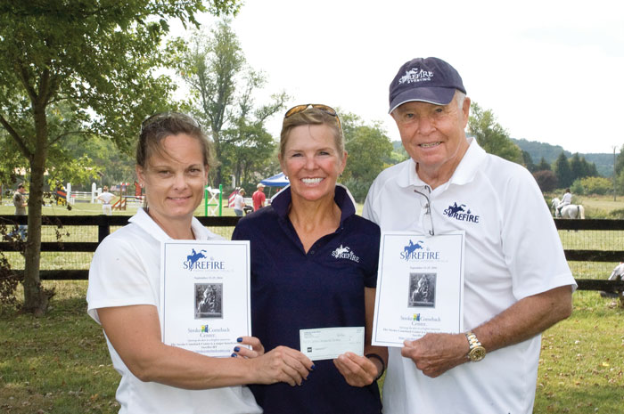 Christy Stauffer, Jan Byyny and Richard Byyny showing a check made out to the Stroke Comeback Center.