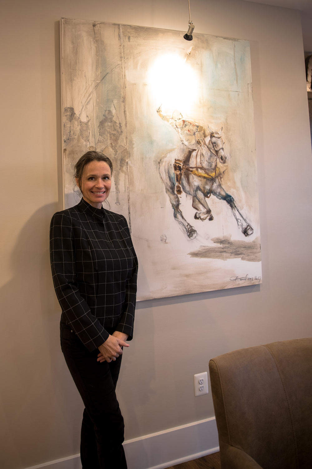 Local artist Isabelle Truchon next to one of many paintings she created for the tasting space.