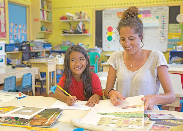 Emily tutoring a student in her classroom.