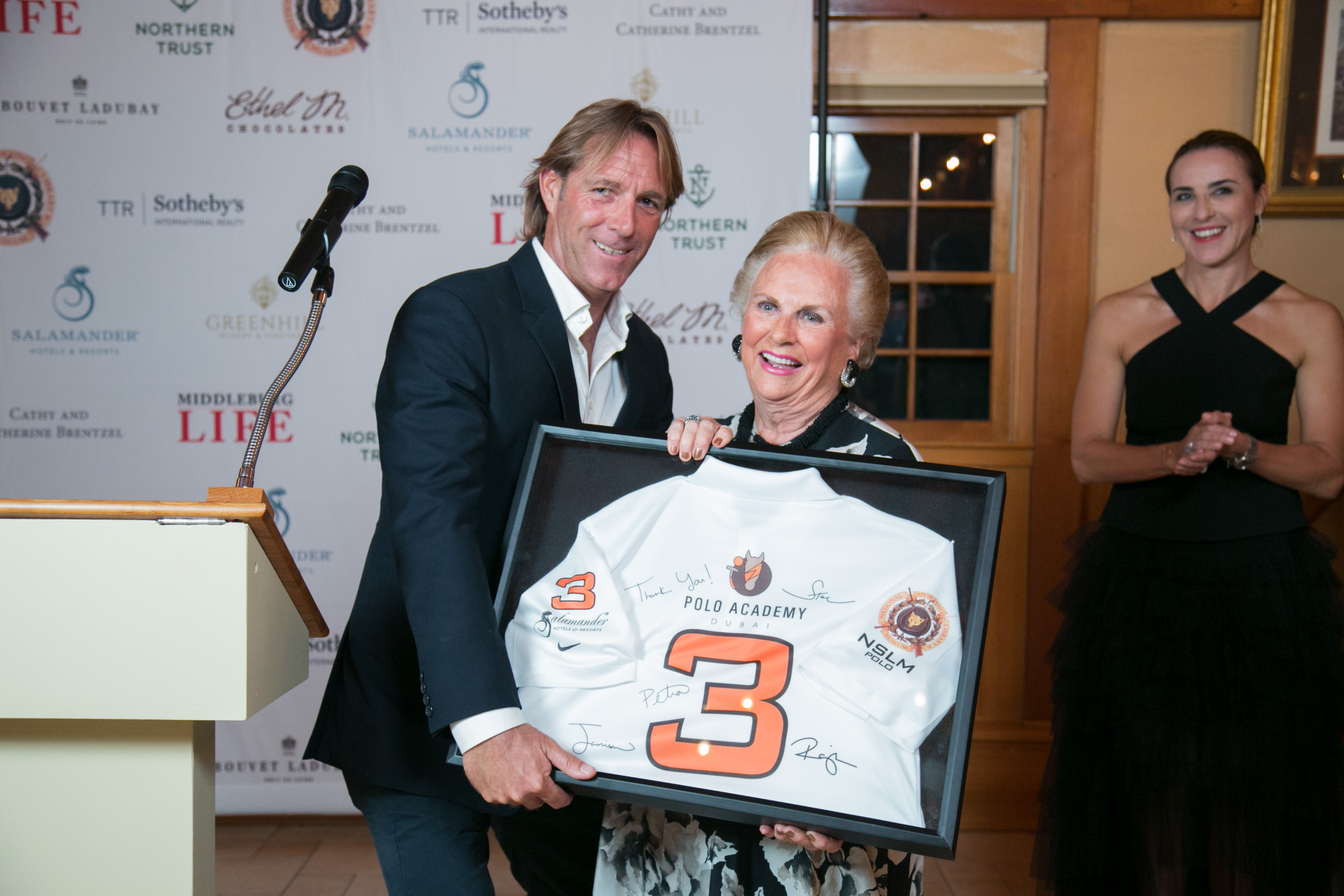 Steve Thompson, of the Dubai polo team, gives Jacqueline Mars a signed polo jersey, Photo courtesy of Julie Napear Photography